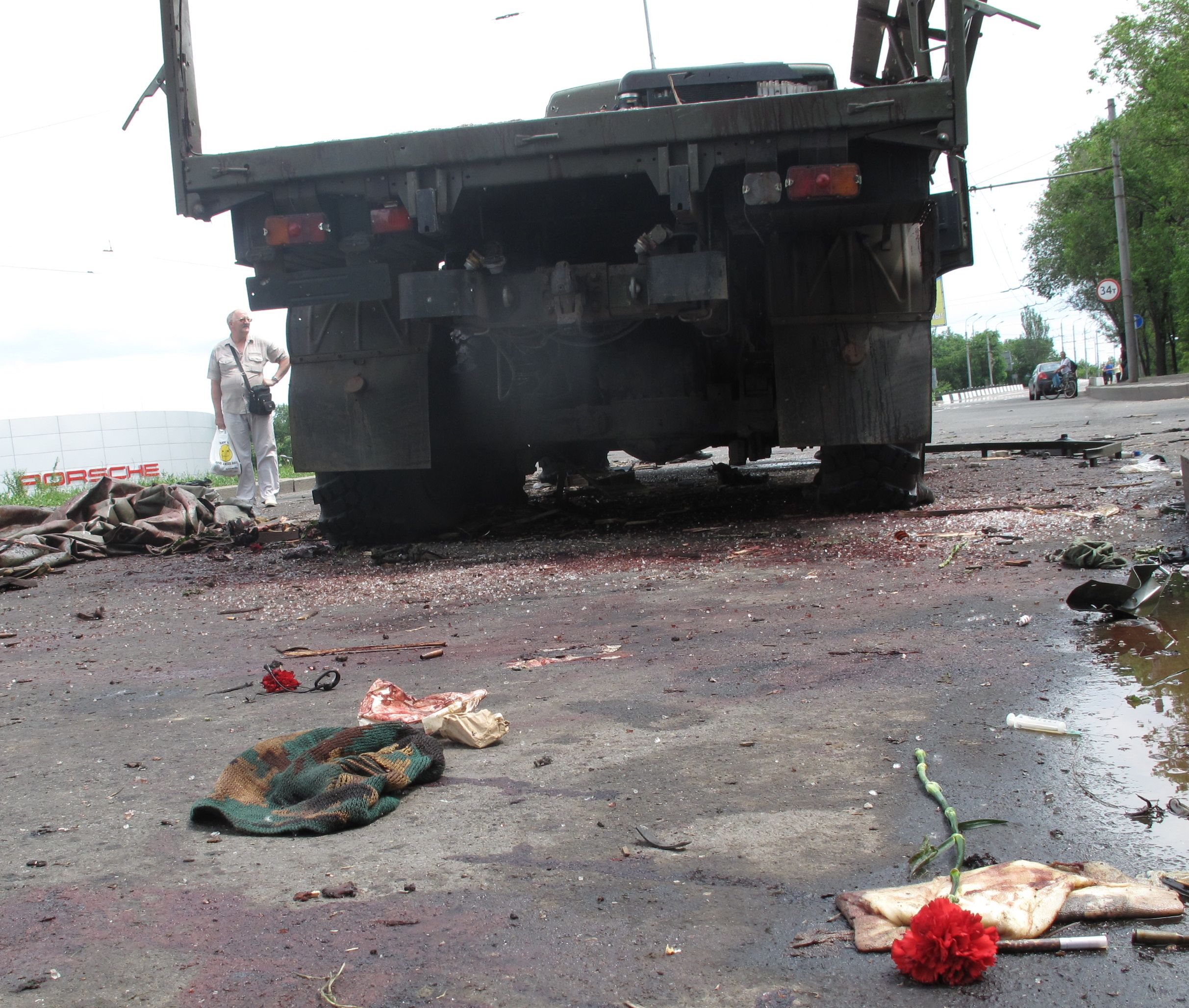 A red carnation is left amidst shell casings, broken glass and human remains following a pre-dawn attack on a separatist vehicle by a Ukrainian helicopter gunship. (Jacob Resneck/FSRN)