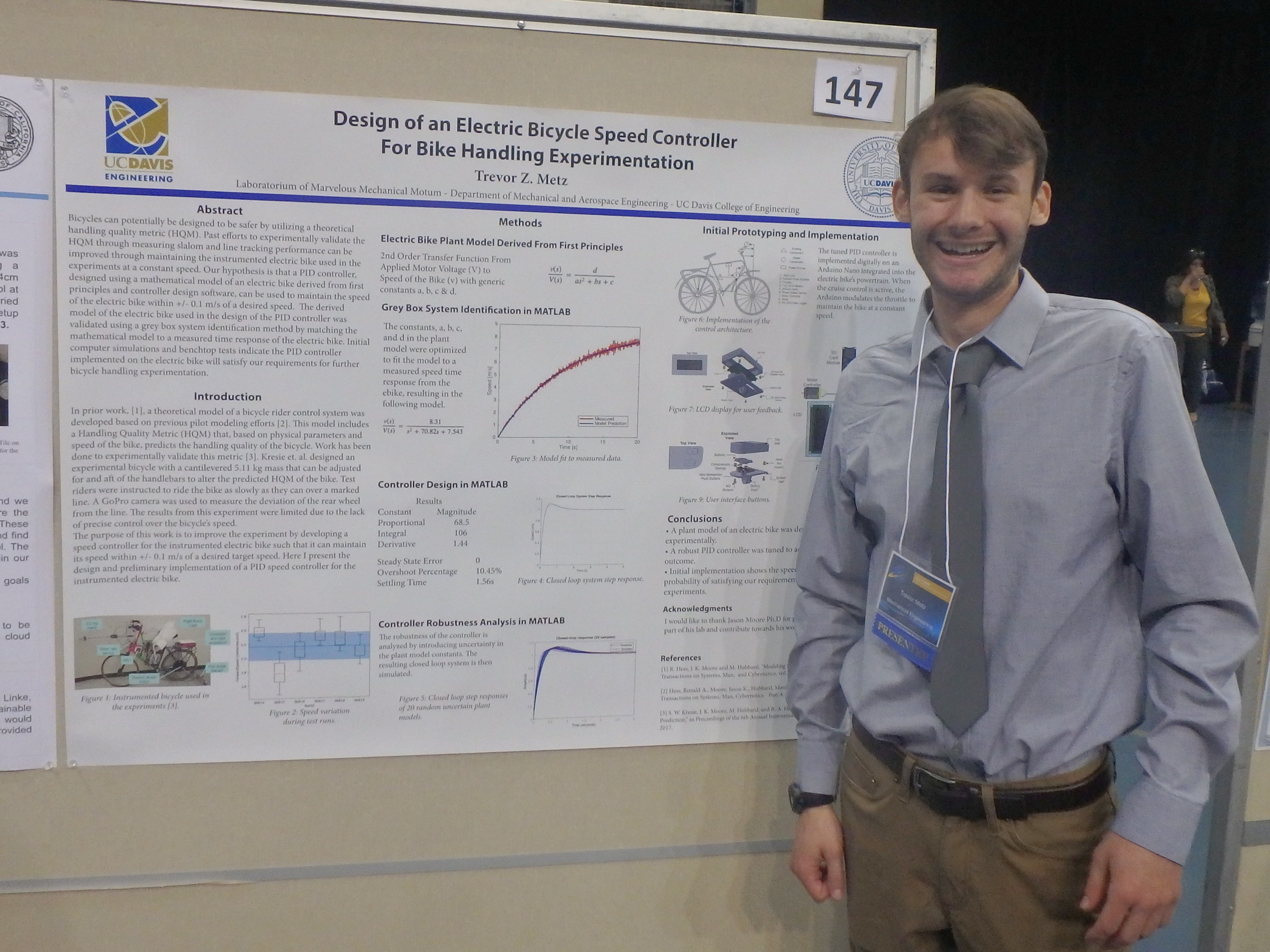Trevor Metz standing beside his poster at the conference.