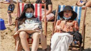 أشخاص على شاطئ يرتدون أقنعة للوجه