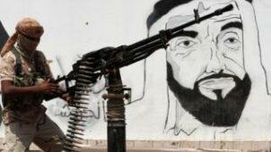 مقاتل يمني يقف بجانب جدارية لمؤسس دولة الإمارات الراحل الشيخ زايد آل نهيان