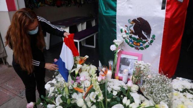 امرأة تحمل العلم الفرنسي بجوار علم المكسيك وبعض الزهور