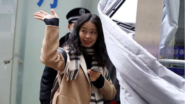 شيان تسي تلوح قبل دخول قاعة المحكمة