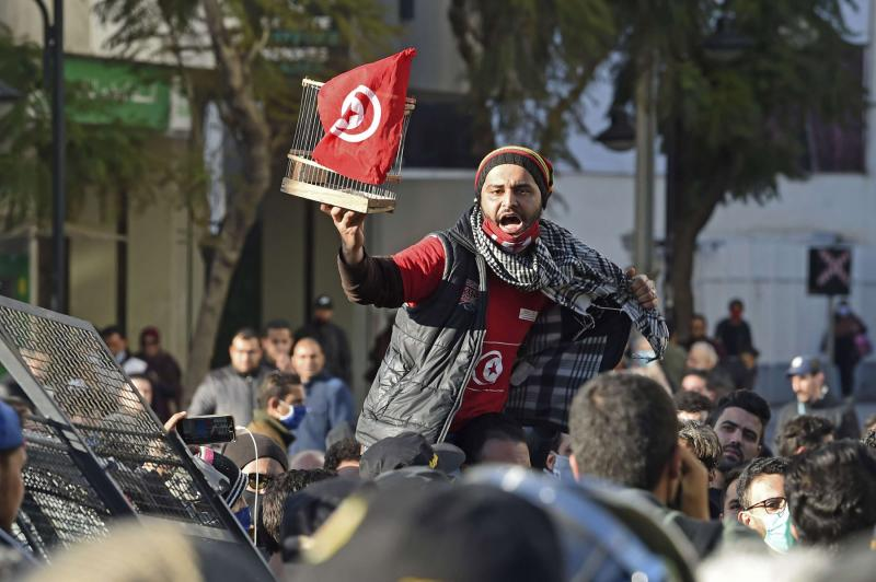 A Tunisian protester lifts a flag confined in a birdcage during an anti-government demonstration on the Habib Bourguiba avenue in the capital Tunis, on January 19, 2021. (AFP)