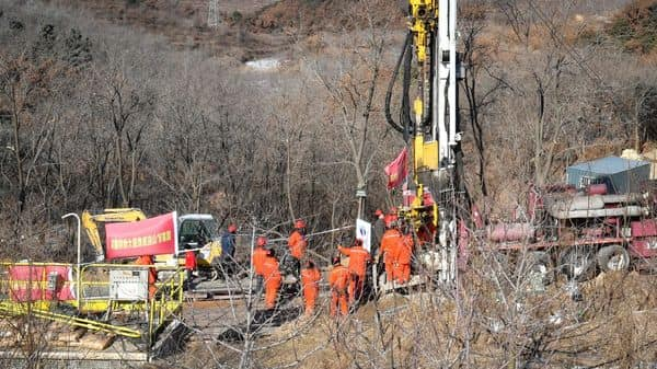 Members of a rescue team work at the site of a gold mine explosion where 22 miners are trapped underground in Qixia, in eastern China