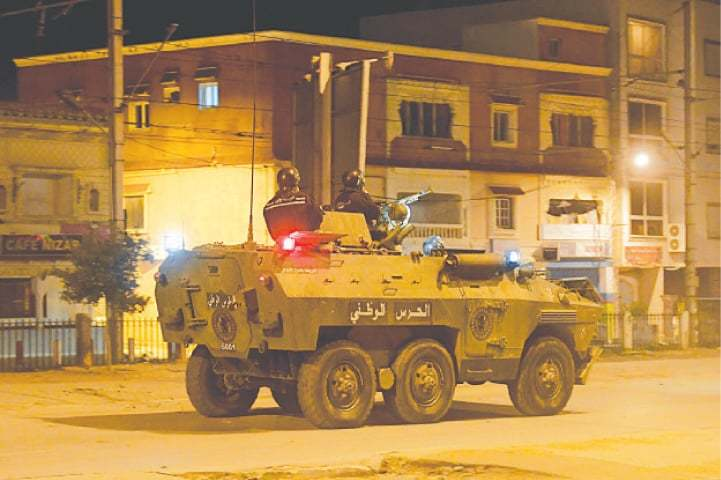 PERSONNEL of the Tunisian National Guard sit atop their armoured vehicle along a street amid clashes with demonstrators.—AFP