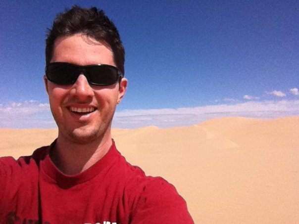 Todd wearing a red shirt with sand dunes in the background